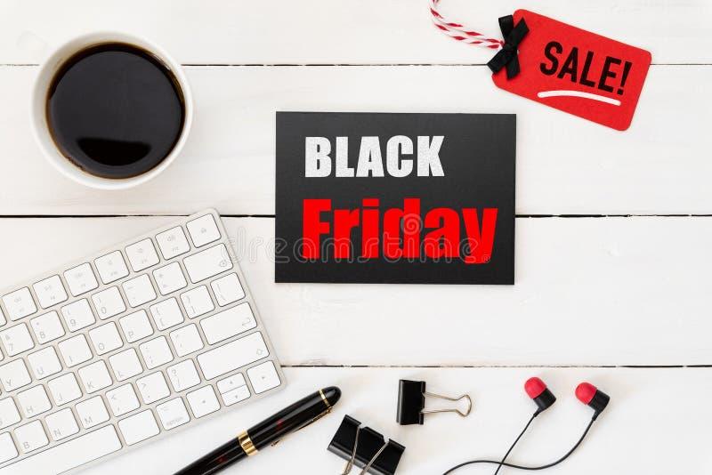 Texto da venda de Black Friday em uma etiqueta vermelha e preta com copo e fone de ouvido de café no fundo de madeira branco da t imagens de stock