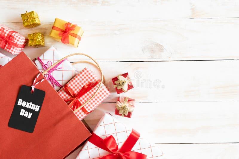 Texto da venda da São Estêvão em uma etiqueta preta com saco de compras e caixa de presente em um fundo branco de madeira Compra  foto de stock