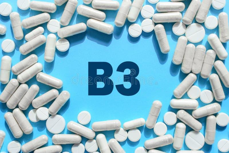 Texto da vitamina B3 no quadro branco das cápsulas no fundo azul Comprimido imagens de stock