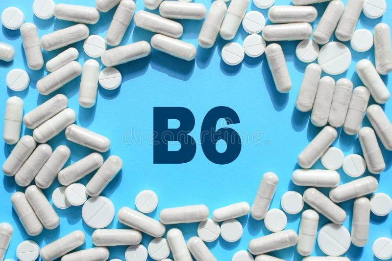 Texto da vitamina B6 no quadro das cápsulas no fundo azul Comprimido com piridoxina; Pyridoxal Suplementos dietéticos e medicamen imagem de stock royalty free