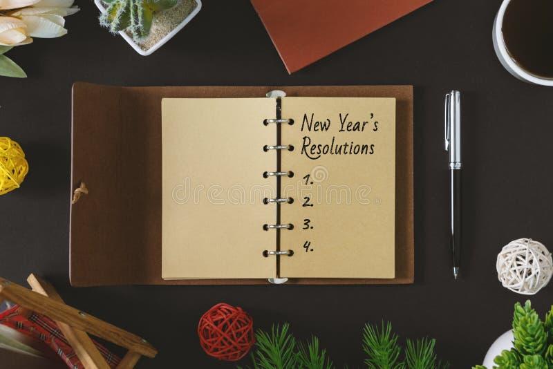 Texto das definições do ano novo no bloco de notas rústico com pena e no café no fundo preto imagens de stock royalty free
