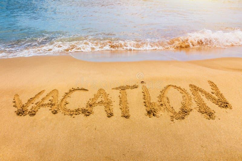 Texto das férias em uma praia F?rias escritas em uma praia tropical arenosa Férias escritas na areia nas ondas azuis da praia den fotos de stock