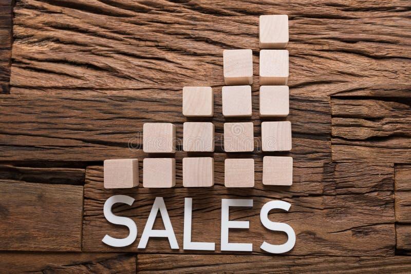 Texto das vendas aumentando blocos do gráfico de barra na madeira fotografia de stock
