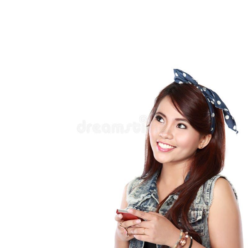 Texto de datilografia da moça feliz em seu telefone celular imagem de stock royalty free