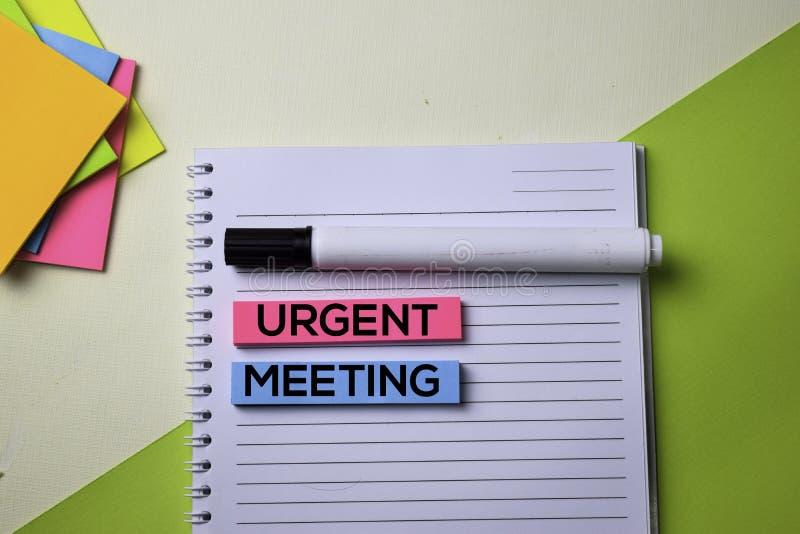 Texto de encuentro urgente en la tabla del escritorio de oficina de la visión superior de lugar de trabajo y de objetos comercial fotografía de archivo libre de regalías