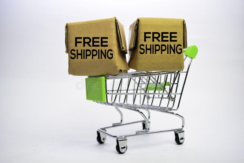 Texto de envio livre em umas caixas pequenas e em um carrinho de compras Conceitos sobre a compra em linha Isolado no fundo branc fotos de stock