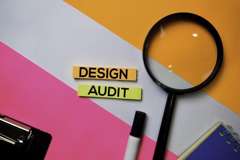 Texto de la auditoría del diseño en notas pegajosas con concepto del escritorio de oficina del color foto de archivo libre de regalías