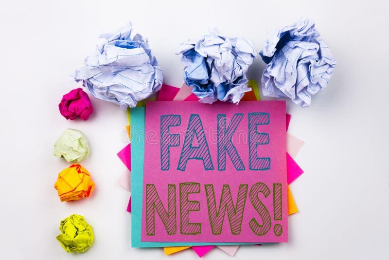 Texto de la escritura que muestra las noticias falsas escritas en nota pegajosa en oficina con las bolas del papel del tornillo C foto de archivo