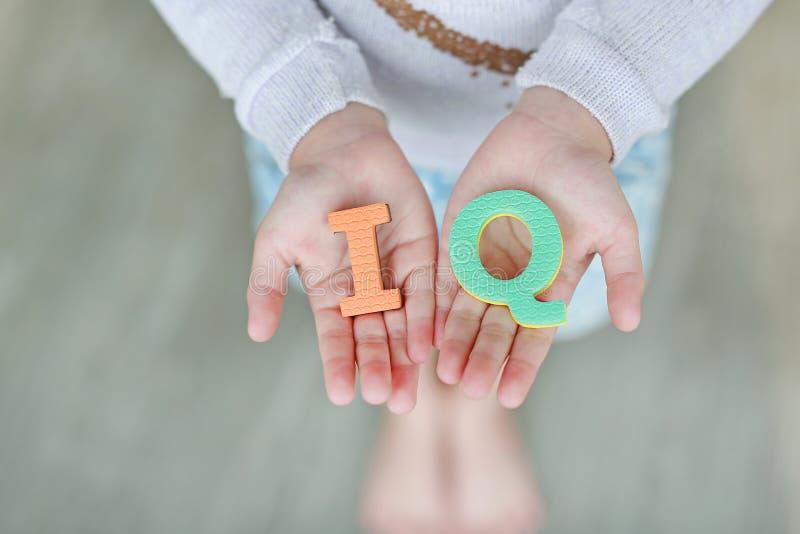Texto de la esponja del cociente de la inteligencia del índice de inteligencia en las manos del niño Concepto de la educaci?n y d imagenes de archivo
