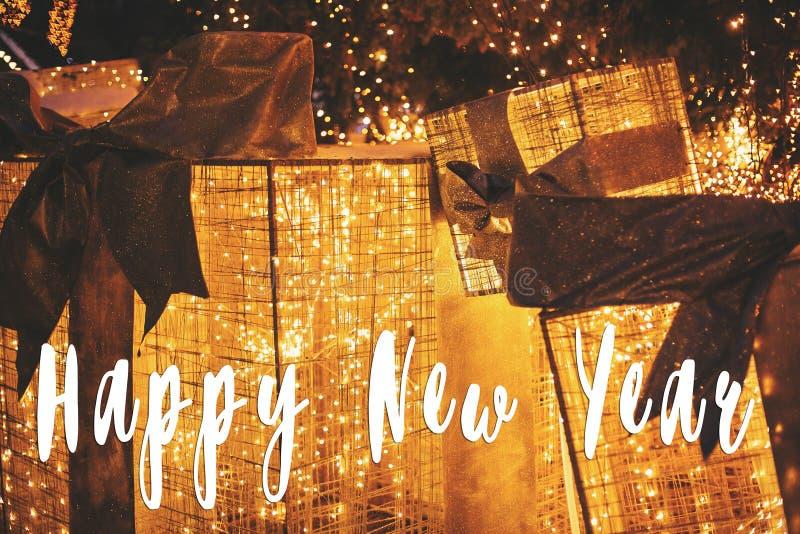 Texto de la Feliz Año Nuevo en las cajas de regalo de oro con las luces debajo de Chris fotografía de archivo libre de regalías