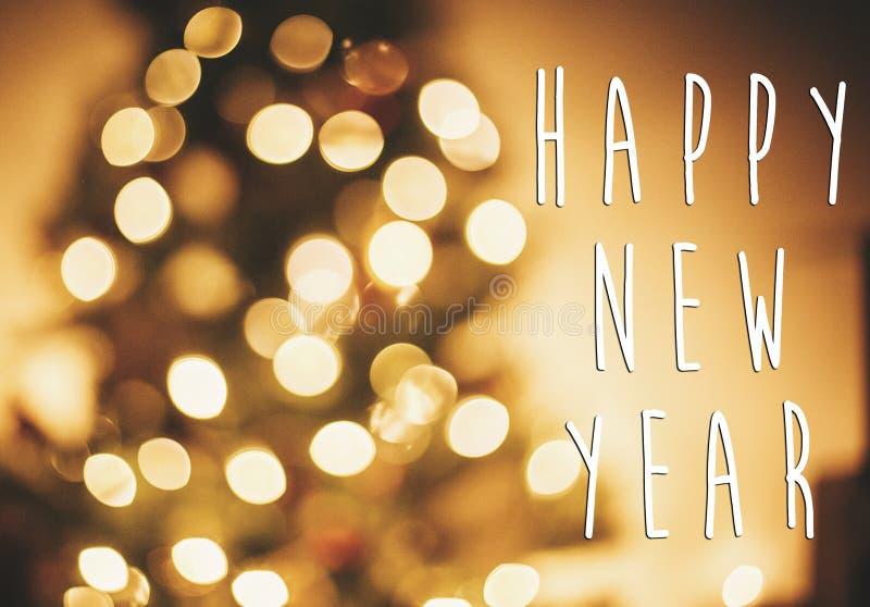 Texto de la Feliz Año Nuevo en luces de oro del árbol de navidad en r festivo imagen de archivo