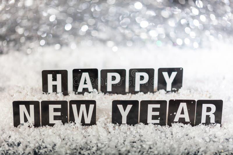 Texto de la Feliz Año Nuevo en la nieve, fondo abstracto de las luces del bokeh fotos de archivo
