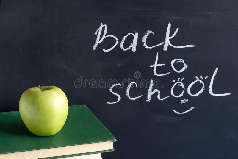 Texto de la inscripción de nuevo a escuela en la pizarra negra y Apple verde en los libros de texto de los libros de la pila, edu imágenes de archivo libres de regalías