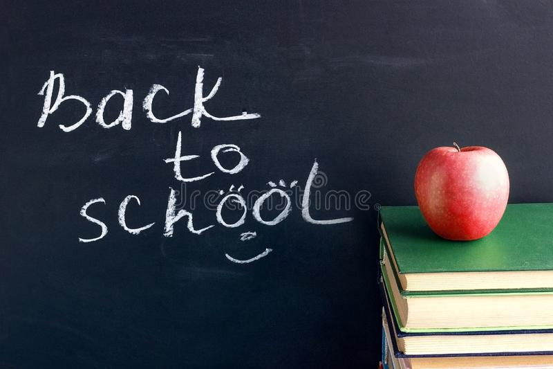Texto de la inscripción de nuevo a escuela en la pizarra negra y la manzana roja en los libros de texto de los libros de la pila, fotografía de archivo libre de regalías