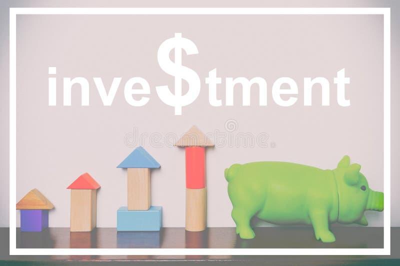 Texto de la inversión con el gráfico y la hucha de levantamiento del bloque del juguete fotos de archivo libres de regalías