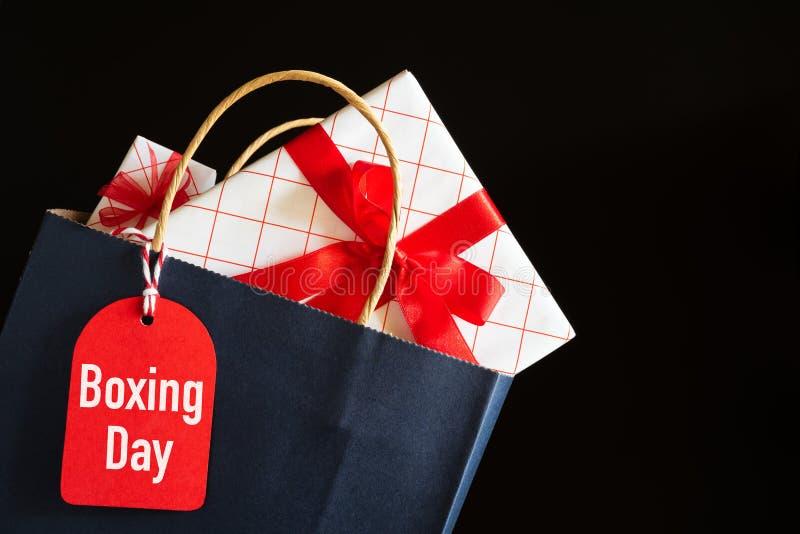 Texto de la venta del San Esteban en una etiqueta negra con el bolso de compras y caja de regalo en fondo negro Compras en línea imagen de archivo libre de regalías