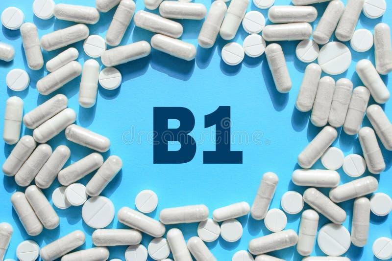 Texto de la vitamina B1 en el marco blanco de las cápsulas en fondo azul Píldora con la tiamina, tiamina Suplementos dietéticos y fotos de archivo