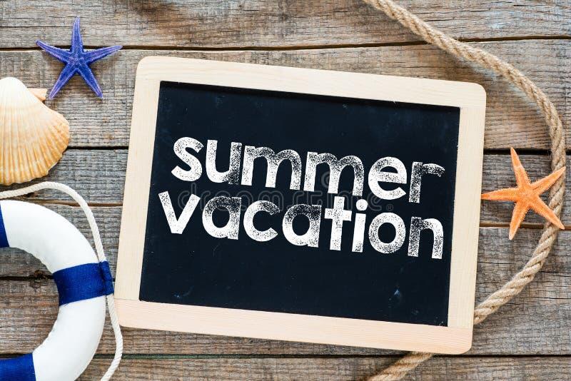 Texto de las vacaciones de verano en la pizarra imagen de archivo