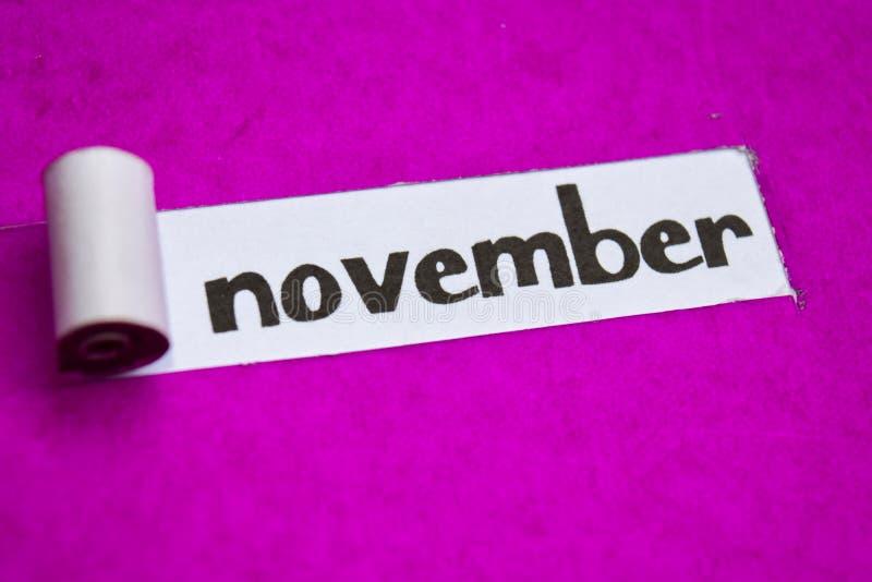 Texto de noviembre, concepto de la inspiración, de la motivación y del negocio en el papel rasgado púrpura imágenes de archivo libres de regalías