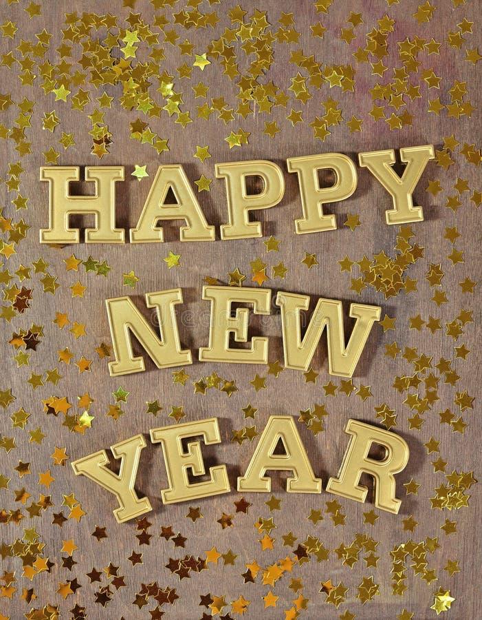 Texto de oro de la Feliz Año Nuevo y estrellas de oro imagenes de archivo
