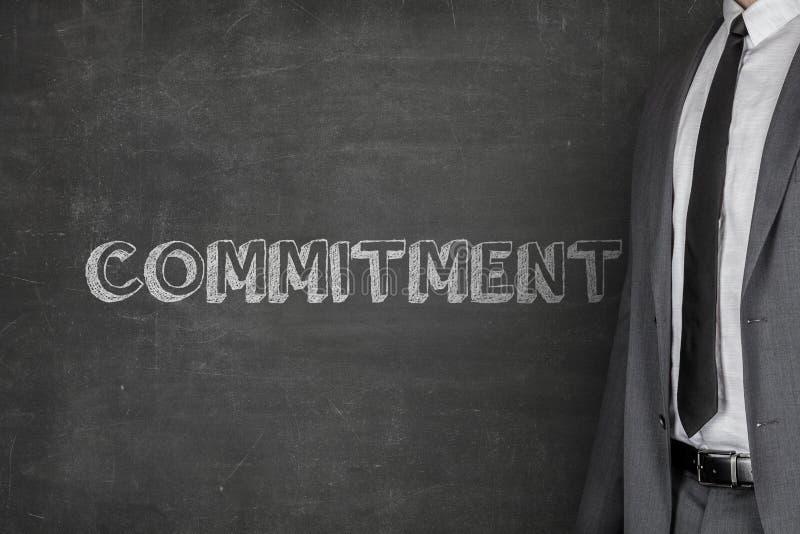 Texto de Standing By Commitment do homem de negócios no quadro-negro fotos de stock