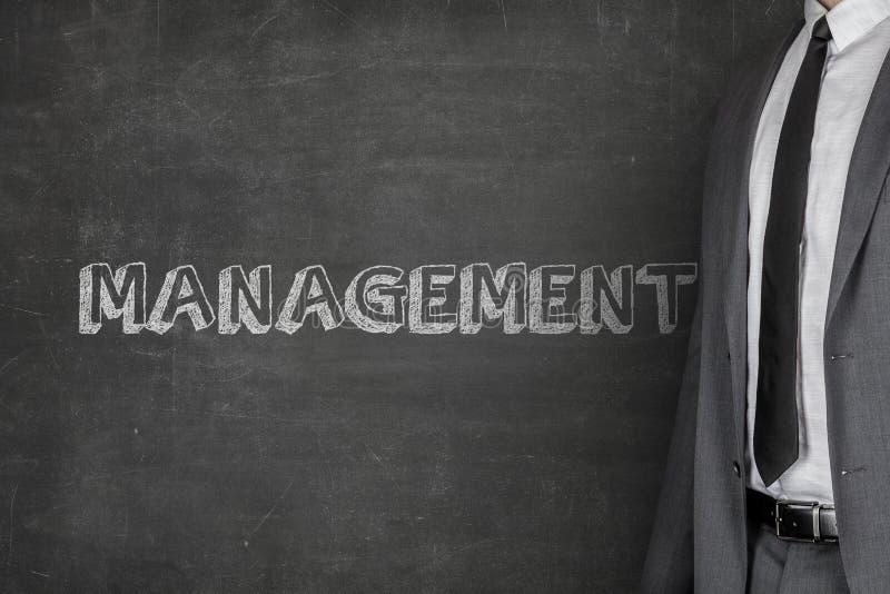 Texto de Standing By Management do homem de negócios no quadro-negro fotos de stock royalty free