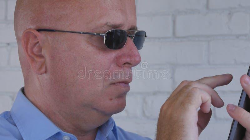 Texto de Wearing Black Sunglasses del hombre de negocios usando el teléfono celular fotos de archivo libres de regalías