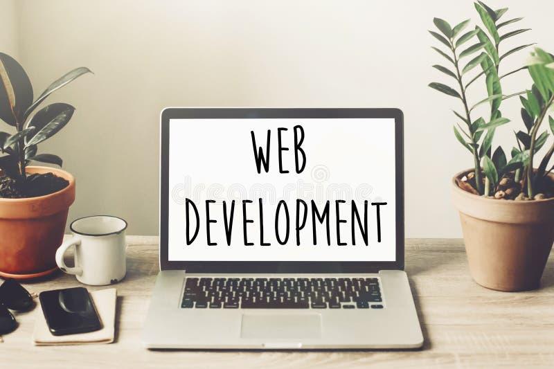 Texto del desarrollo web en la pantalla del ordenador portátil en la mesa de madera con pho fotos de archivo libres de regalías