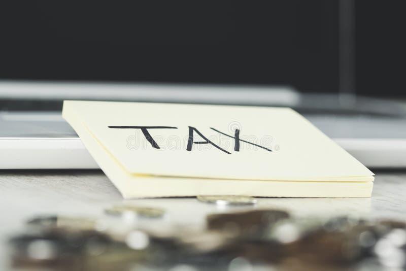 Texto del impuesto con las monedas fotos de archivo