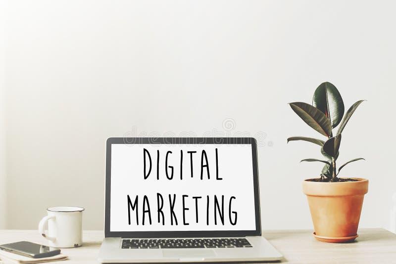 Texto del márketing de Digitaces en la pantalla del ordenador portátil en la mesa de madera con p foto de archivo libre de regalías