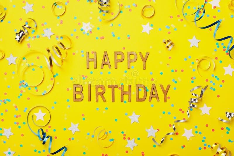 Texto del saludo del feliz cumpleaños adornado con confeti y la serpentina en la opinión superior del fondo amarillo estilo plano fotos de archivo libres de regalías