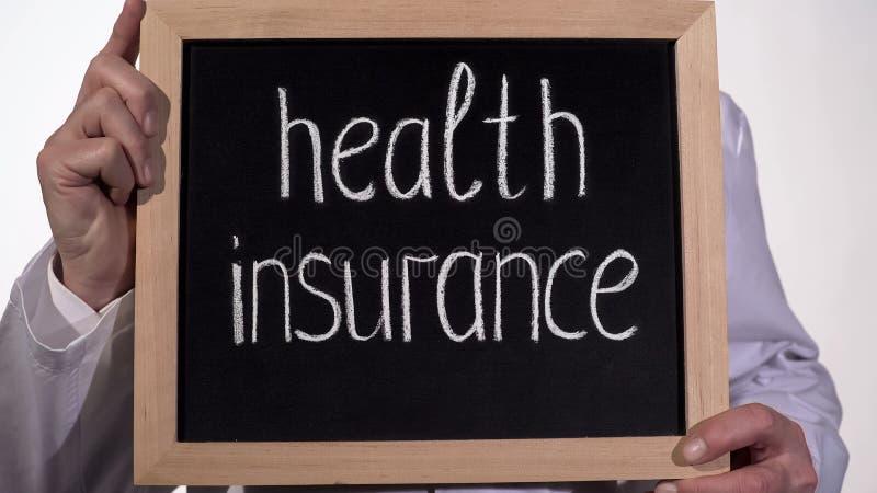 Texto del seguro médico en la pizarra en manos del doctor, medicina de familia costosa foto de archivo libre de regalías