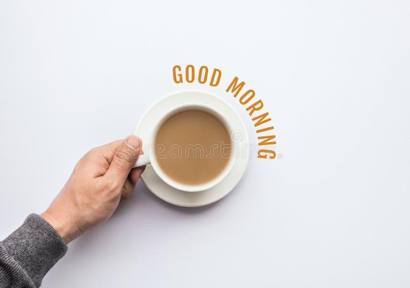 Texto do bom dia com a mão masculina que guarda a xícara de café Negócios fotos de stock royalty free