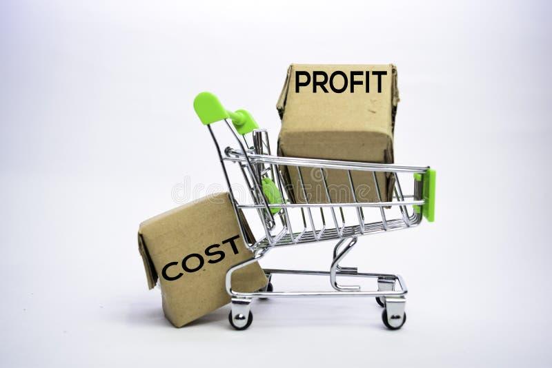 Texto do custo e do lucro em umas caixas pequenas e em um carrinho de compras Conceitos sobre a compra em linha Isolado no fundo  imagem de stock royalty free