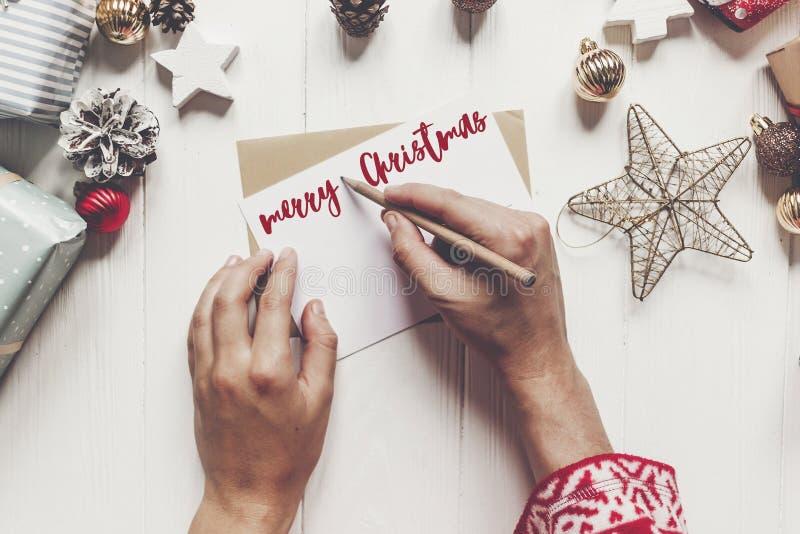 Texto do Feliz Natal, sinal sazonal do cartão de cumprimentos entrega o holdin imagem de stock royalty free