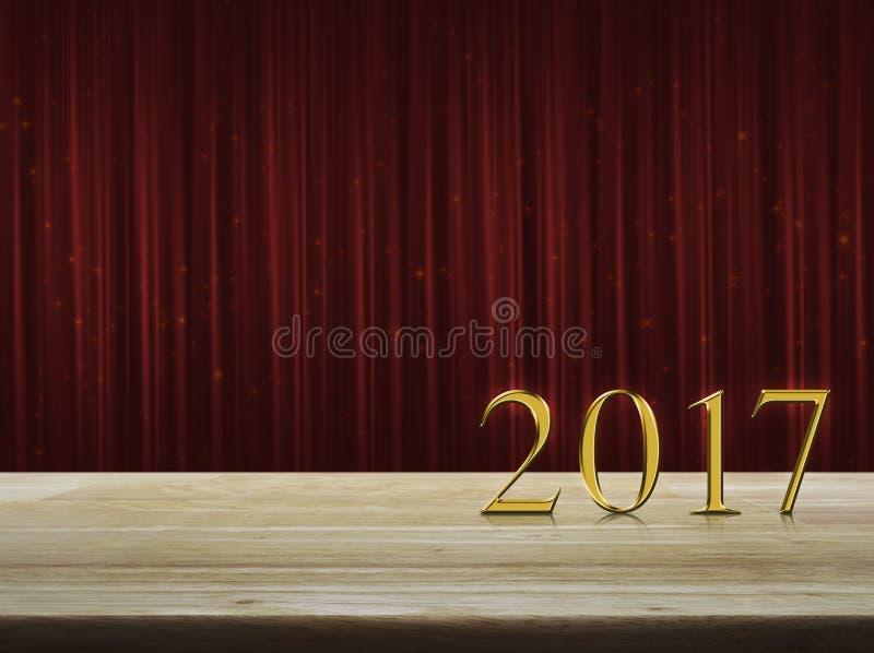 Texto 2017 do metal do ouro do ano novo feliz na tabela sobre a cortina vermelha imagens de stock
