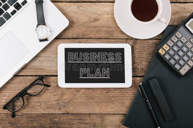 Texto do plano de negócios no tablet pc, mesa de escritório com computador foto de stock royalty free