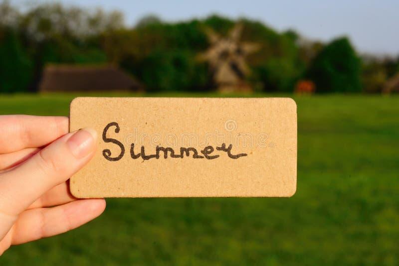 Texto do verão em um cartão Menina que guarda o cartão em um campo com windmi fotografia de stock