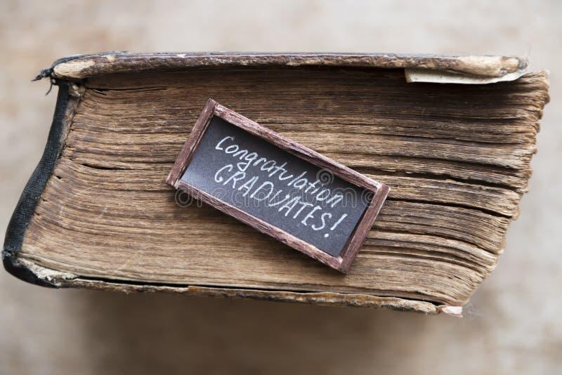 Texto dos graduados das felicitações e livro do vintage imagem de stock royalty free