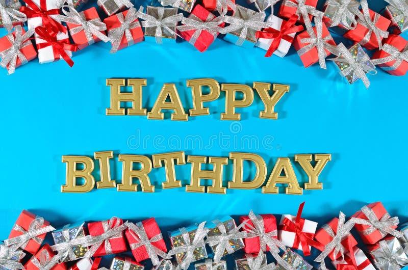 Texto dourado do feliz aniversario e presentes de prata e vermelhos em um azul imagem de stock royalty free