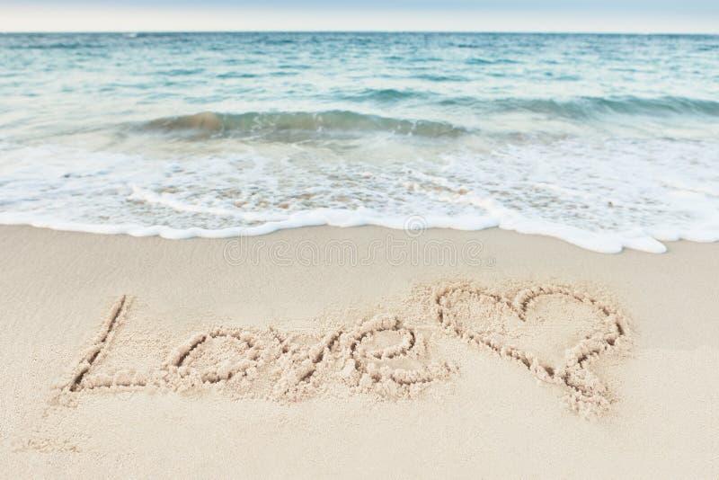 Texto e coração do amor tirados na areia pelo mar imagem de stock