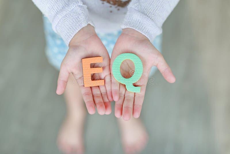 Texto emocional de la esponja del cociente de EQ en las manos del niño Concepto de la educaci?n y del desarrollo foto de archivo libre de regalías