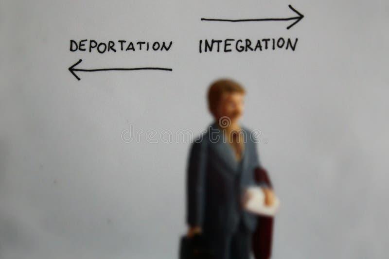 Texto escrito à mão da deporta16cao e da integração com as setas esquerdas e direitas O homem diminuto obscuro está indo à maneir fotografia de stock royalty free