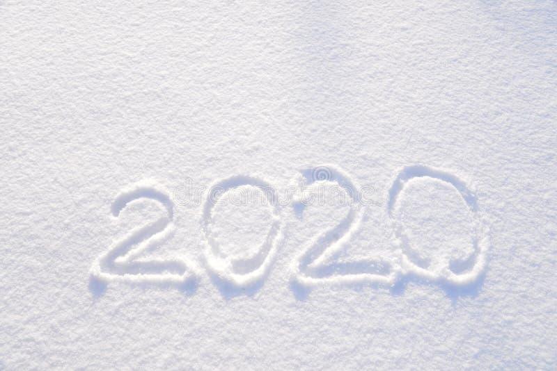 texto 2020 escrito en el fondo de la textura fresca de la nieve - vacaciones de invierno, Feliz Navidad, día soleado del concepto imagen de archivo libre de regalías
