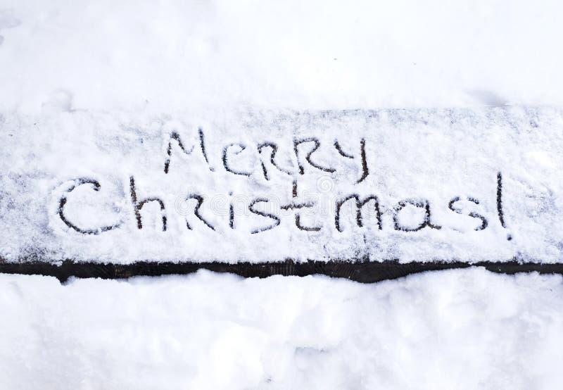 Texto escrito Feliz Navidad en la nieve imagen de archivo