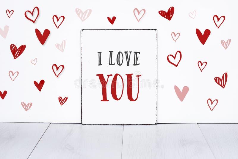 Texto eu te amo na placa do sinal com poucos corações tirados mão na bandeira branca do dia de Valentim do fundo imagem de stock