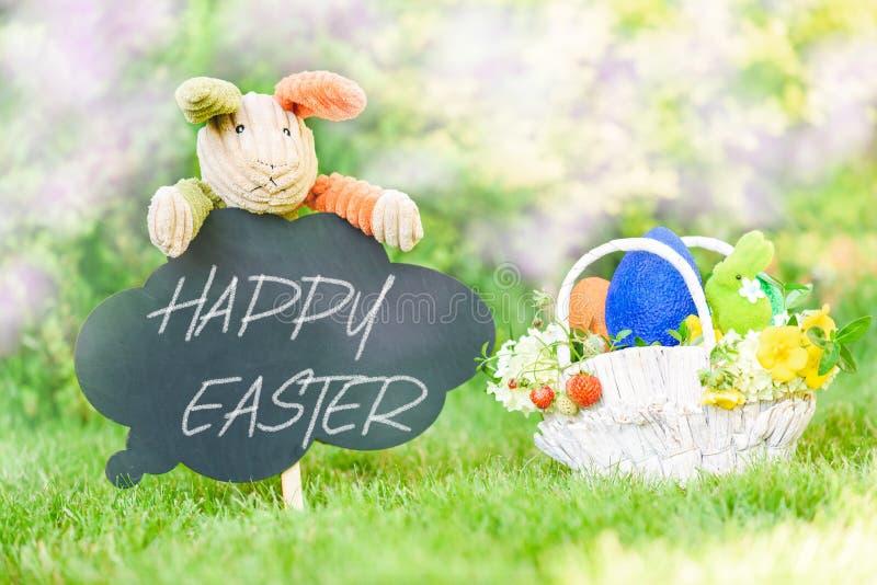 Texto feliz da Páscoa no quadro-negro e cesta com símbolos de Eastertide imagem de stock