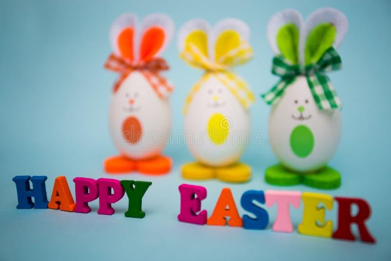 Texto feliz de pascua de letras de madera coloridas con los huevos divertidos bajo la forma de conejito lindo en fondo azul fotos de archivo libres de regalías