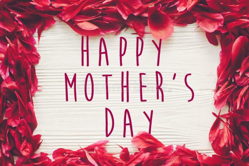 Texto feliz del día del ` s de la madre en los pétalos rojos de las peonías en el blanco rústico wo libre illustration