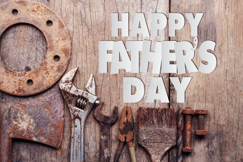 Texto feliz do dia de pai com as ferramentas oxidadas velhas no fundo de madeira fotos de stock royalty free